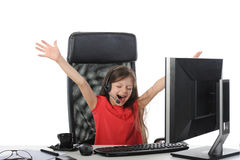 Joyful girl in the office in front of computer Royalty Free Stock Photography