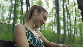 Joyful girl with ponytail, listening music with earphones and laughing. Jogger resting on a bench in the park. Beautiful fitness girl using mobile phone outdoors stock footage