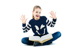 Joyful girl with raised hands. Girl sitting on the floor with a big book Royalty Free Stock Images