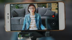 Joyful girl recording video with smartphone camera talking gesturing at home