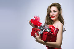 Joyful girl in red dress with gifts Royalty Free Stock Images