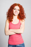 Joyful girl with red hair on gray wall Stock Image