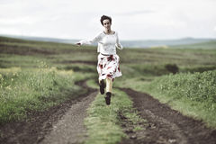 Joyful girl running on a countryside road. Freedom concept stock photos