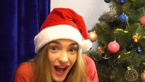 Joyful girl in santa hat hides behind a christmas gifts stock video