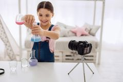 Joyful girl showing how colors change in chemical flasks. Exciting chemical experiment. Upbeat pre-teen girl mixing chemicals and showing how colors change in royalty free stock image