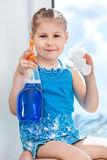 Joyful girl shows cloth and window cleaner on plastic windowsill Royalty Free Stock Images
