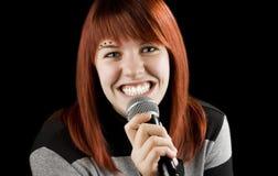Joyful girl singing on the karaoke. Redhead girl using her microphone singing karaoke and smiling big time Stock Photography