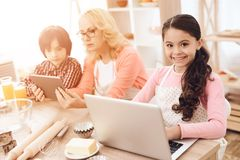 Joyful girl sits behind laptop next to her grandmother and brother watching tablet in kitchen. Stock Photos