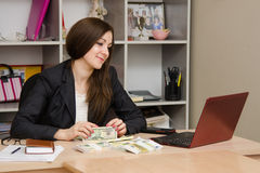 Joyful Girl sitting a desk with pile of money and looking at computer Royalty Free Stock Photography