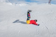 Joyful girl snowboarder lies on the snow with arms outstretched. Smile Stock Photo