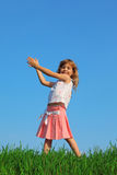Joyful girl stands in field with green grass Stock Photo