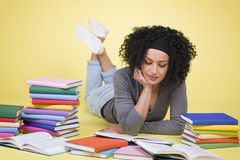 Joyful girl studying surrounded by colorful books. Royalty Free Stock Photography