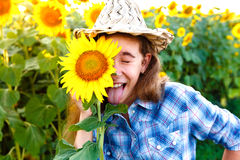 Joyful girl with sunflowers and closed eyes showing tongue Stock Photo