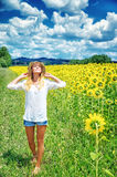 Joyful girl in sunflowers field. Joyful girl walking in sunflowers field, active lifestyle, agricultural landscape, enjoying blooming nature, autumn season Royalty Free Stock Photography