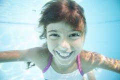 Joyful girl swimming underwater in pool. Stock Image