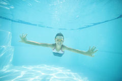 Joyful girl swimming underwater in pool. Stock Photo