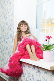 Joyful girl teenager sitting on windowsil in room Stock Image