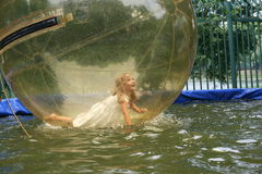 Joyful girl to dunk in a transparent ball. Day Royalty Free Stock Photography