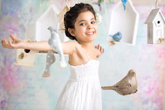 Joyful girl among wooden birds Royalty Free Stock Images