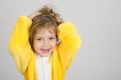 Joyful girl in a yellow bathrobe Royalty Free Stock Photography