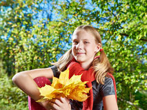 Joyful girl with yellow leaves in autumn park on sunny day royalty free stock images
