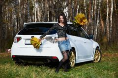 Joyful girl with yellow leaves and white car Stock Photography