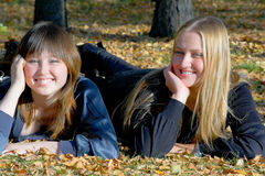 Joyful girlfriends. Two joyful girlfriends against the autumn nature Royalty Free Stock Photos