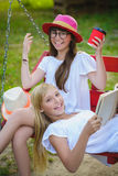 Joyful girlfriends having fun on swing outdoor. Friendship concept royalty free stock photo