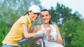 Joyful girlfriends in sports clothing drinking water Royalty Free Stock Photo