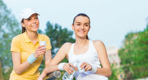 Joyful girlfriends in sports clothing drinking water Royalty Free Stock Images