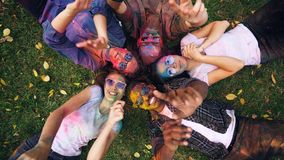 Joyful girls and guys are lying on grass in park, their faces and clothing are covered with multicolor paint, people are stock image