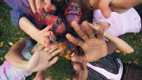 Joyful girls and guys are lying on grass in park, their faces and clothing are covered with multicolor paint, people are