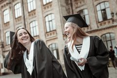Joyful girls having fun while standing near university. Happy together. Positive delighted blonde female keeping smile on her face while looking at her friend stock photo