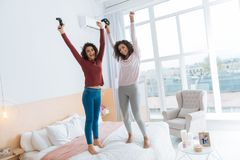 Joyful girls jumping on bed after playing video games. No time for worries. Full length shot of two curly haired ladies in casual beaming while holding video Stock Photo