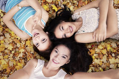 Joyful girls lying down autumn leaves. Closeup of teenage girls lying down on the autumn leaves and taking self picture together Stock Photos