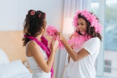 Joyful girls playing with pink feather boa Royalty Free Stock Photography