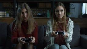 Joyful girls playing video games with joysticks stock video