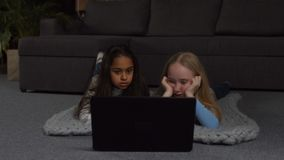 Joyful girls watching comedy show online on laptop. Excited adorable long hair multi ethnic kids watching comedy movie on line on laptop pc while lying on the stock video footage