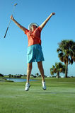 Joyful Golfer. A senior woman jumps for joy on the golf course stock photography