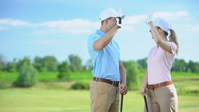 Joyful golfers with clubs giving high-five after successful sport championship. Stock footage stock footage