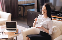 Joyful good looking businesswoman having coffee. Coffee break. Joyful good looking successful businesswoman holding a cup with coffee and smiling while having a Stock Images