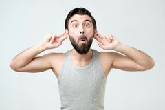 Joyful man stretching ears while smiling and looking like monkey stock photos