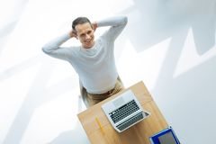 Joyful good looking man deciding to rest. I need to relax. Joyful good looking positive man smiling and deciding to rest while finishing his project Royalty Free Stock Image