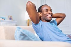 Joyful good looking man enjoying his rest. Pleasurable time. Joyful positive good looking man smiling and enjoying his rest while being at home Stock Images