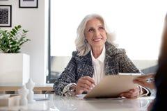 joyful gorgeous old woman holding documents good mood charming positive delightful senior lady sitting workplace light 103188389
