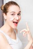 Joyful gorgeous young woman enjoying applying cream for fun morning Stock Image