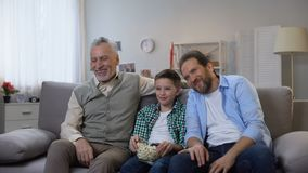 Joyful grandpa, father and son enjoying comedy show on tv, having fun together