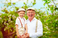 Joyful grandpa and grandson having fun in spring apple garden Royalty Free Stock Photos