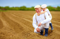 Joyful grandpa and grandson having fun on spring plowed field Royalty Free Stock Photography