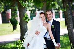 Joyful groom and bride in park stock image